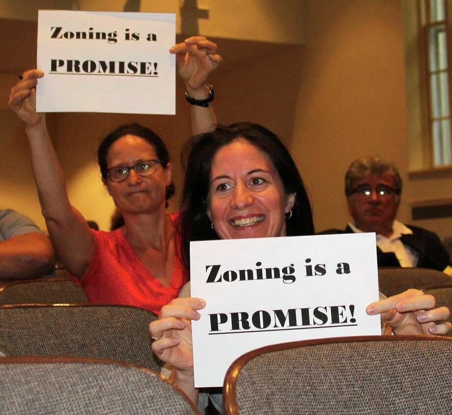 Westport residents Bonnie Dubson (back) and Anca Micu (front) held up signs at the June 14 Planning and Zoning Commission meeting in Westport Town Hall. The pair protested the commission's decision to approve a 9 unit small housing development for people 55 and older at 500 Main St., which lies close to both Dubson and Micu's homes. Photo: Sophie Vaughan / Hearst Connecticut Media / Westport News