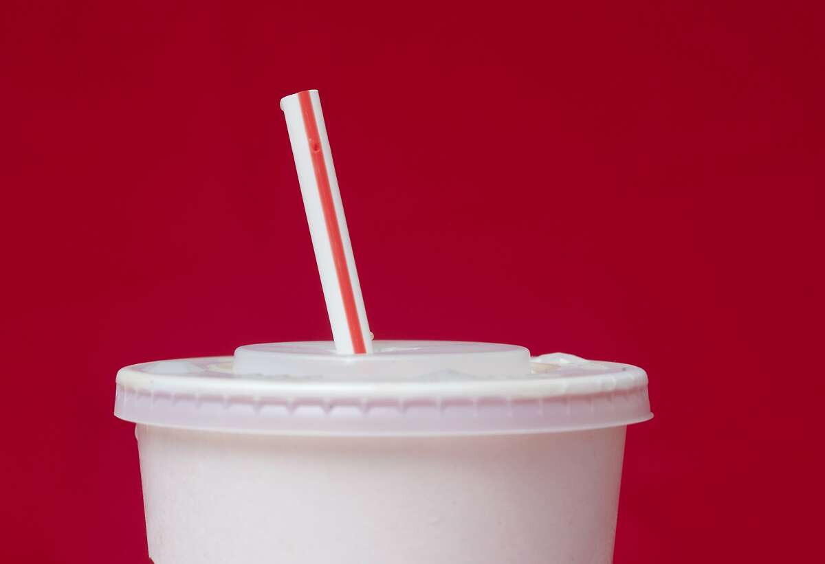 FILE- In this May 24, 2018, file photo, a large soft drink with a plastic straw from a McDonald's restaurant is shown in Surfside, Fla. McDonald's said Friday, June 15, that it will switch to paper straws at all its locations in the United Kingdom and Ireland, and test an alternative to plastic ones in some of its U.S. restaurants later this year. (AP Photo/Wilfredo Lee, File)