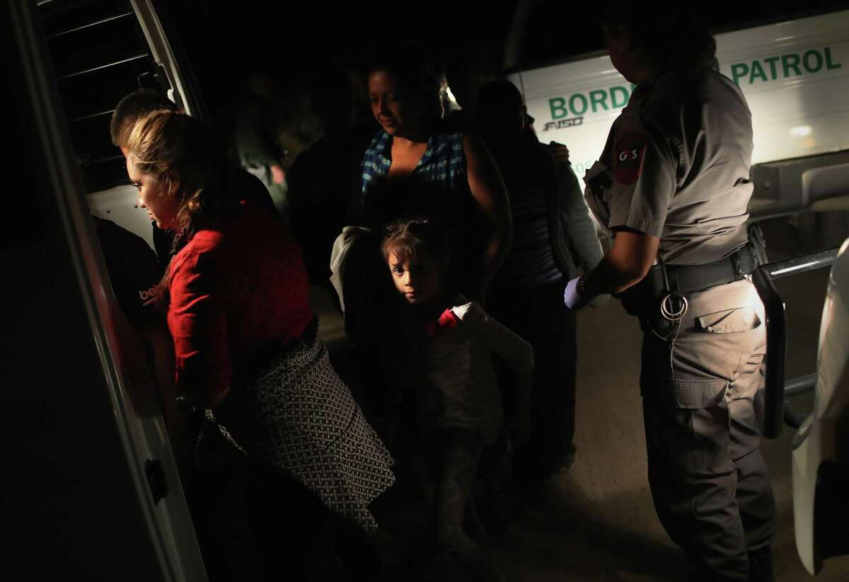 """U.S. Border Patrol agents detain a group of Central American asylum seekers near the U.S.-Mexico border on June 12, 2018 in McAllen, Texas. The group of women and children had rafted across the Rio Grande from Mexico and were detained before being sent to a processing center for possible separation. Customs and Border Protection is executing the Trump administration's """"zero tolerance"""" policy toward undocumented immigrants. U.S. Attorney General Jeff Sessions also said that domestic and gang violence in immigrants' country of origin would no longer qualify them for political asylum status."""