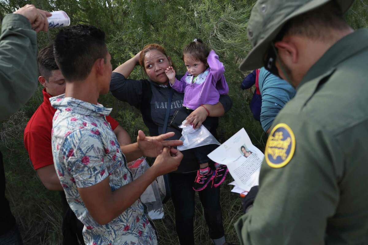 """U.S. Border Patrol agents ask a group of Central American asylum seekers to remove hair bands and weddding rings before taking them into custody on June 12, 2018 near McAllen, Texas. The immigrant families were then sent to a U.S. Customs and Border Protection processing center for possible separation. U.S. border authorities are executing the Trump administration's """"zero tolerance"""" policy towards undocumented immigrants. U.S. Attorney General Jeff Sessions also said that domestic and gang violence in immigrants' country of origin would no longer qualify them for political asylum status."""