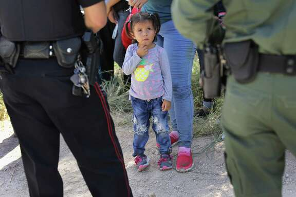 """A Mission Police Dept. officer (L), and a U.S. Border Patrol agent watch over a group of Central American asylum seekers before taking them into custody on June 12, 2018 near McAllen, Texas. Local police officers often coordinate with Border Patrol agents in the apprehension of undocumented immigrants near the border. The immigrant families were then sent to a U.S. Customs and Border Protection processing center for possible separation. U.S. border authorities are executing the Trump administration's """"zero tolerance"""" policy toward undocumented immigrants. U.S. Attorney General Jeff Sessions also said that domestic and gang violence in immigrants' country of origin would no longer qualify them for political asylum status."""