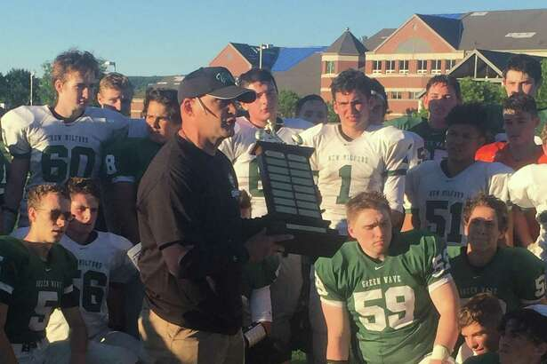 New Milford High School football coach Chuck Lynch awards the Joe South Memorial Trophy to the White Team at the conclusion of the annual Green and White Spring Football Game at New Milford High School June 15, 2018.