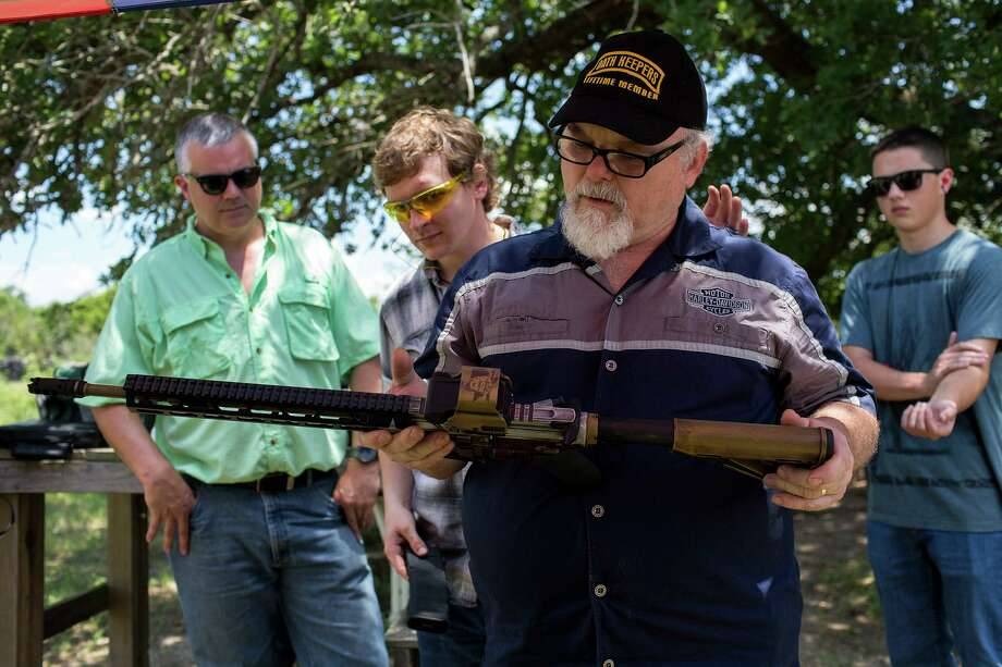 Stephen Willeford looks at an AR-15 rifle, specially designed for him and given to him by Stephen Oliver, a gun manufacturer and dealer with Texas Rifle, after Oliver presented it to him at Willeford's property near Sutherland Springs on May 28, 2018. Watching are, from left, firearms manufacturer Thomas Trevino, owner of Double T Tactical in Floresville, Willeford's son, Blake Willeford, and Trevino's son, Thomas Trevino, 16. Photo: Lisa Krantz / SAN ANTONIO EXPRESS-NEWS / SAN ANTONIO EXPRESS-NEWS