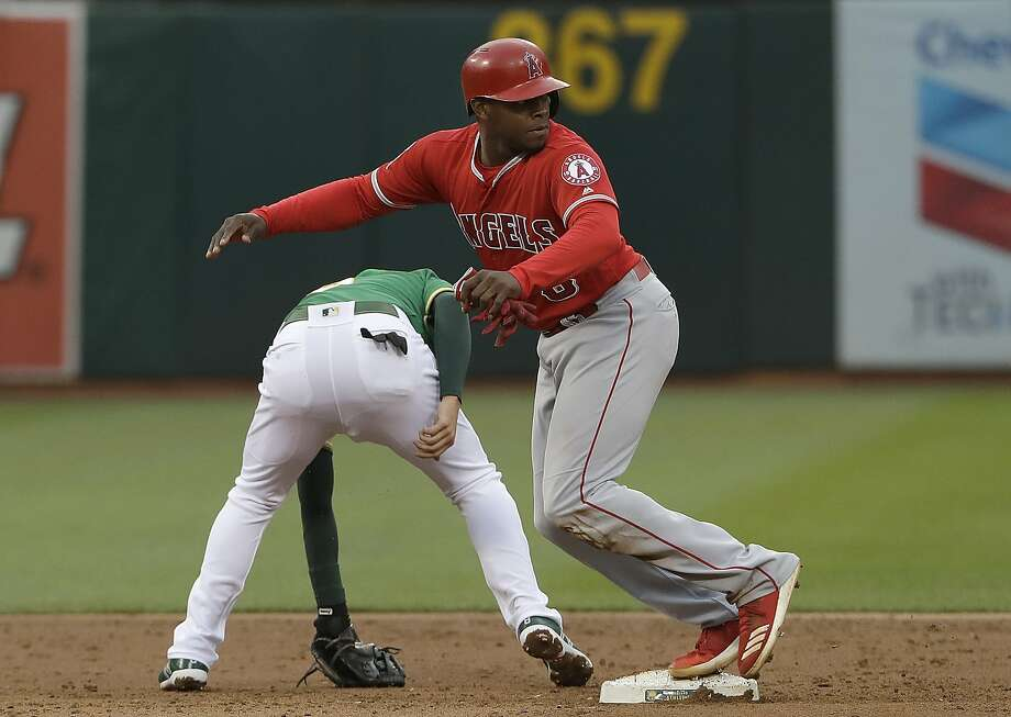 Los Angeles Angels' Justin Upton, top, runs toward third base after Oakland Athletics second baseman Jed Lowrie, bottom, could not field a throwing error by third baseman Chad Pinder during the third inning of a baseball game in Oakland, Calif., Friday, June 15, 2018. (AP Photo/Jeff Chiu) Photo: Jeff Chiu / Associated Press