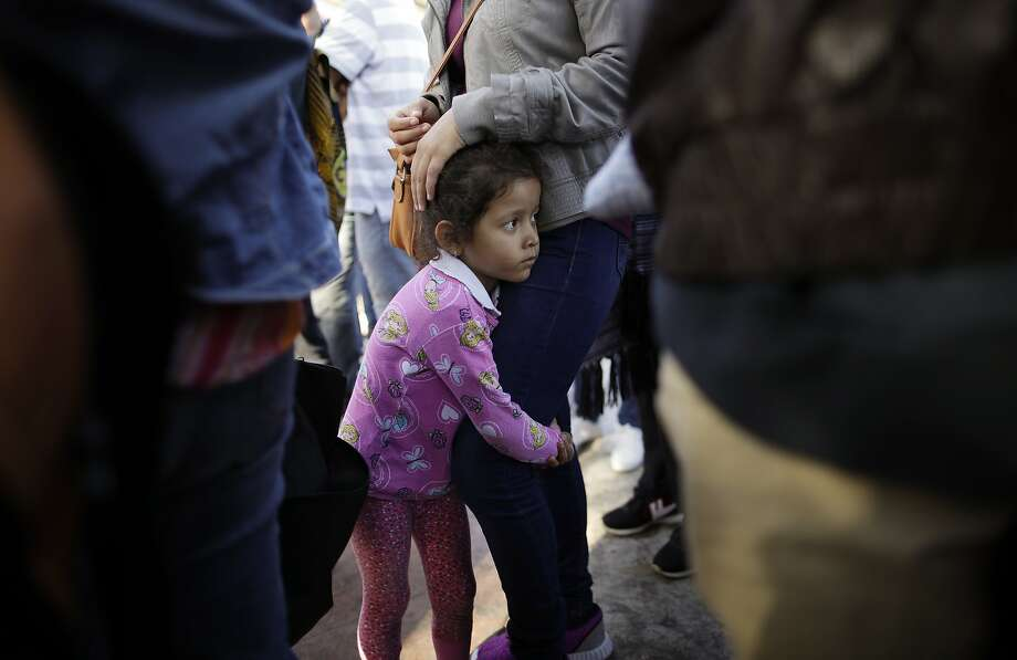 Nicole Hernandez holds her mother as they wait Wednesday in Tijuana, Mexico, to request political asylum in the United States. Photo: Gregory Bull / Associated Press