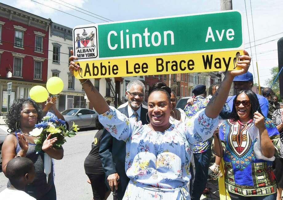 Abby Brace-Castillo holds up a street sign at the intersection of Henry Johnson Blvd and Clinton Avenue in memory of her grandmother, community figure Abbie Lee Brace who died in 2006, during a ceremony on Saturday, June 16, 2018, in Albany, N.Y. Photo: Hans Pennink, Times Union / Hans Pennink