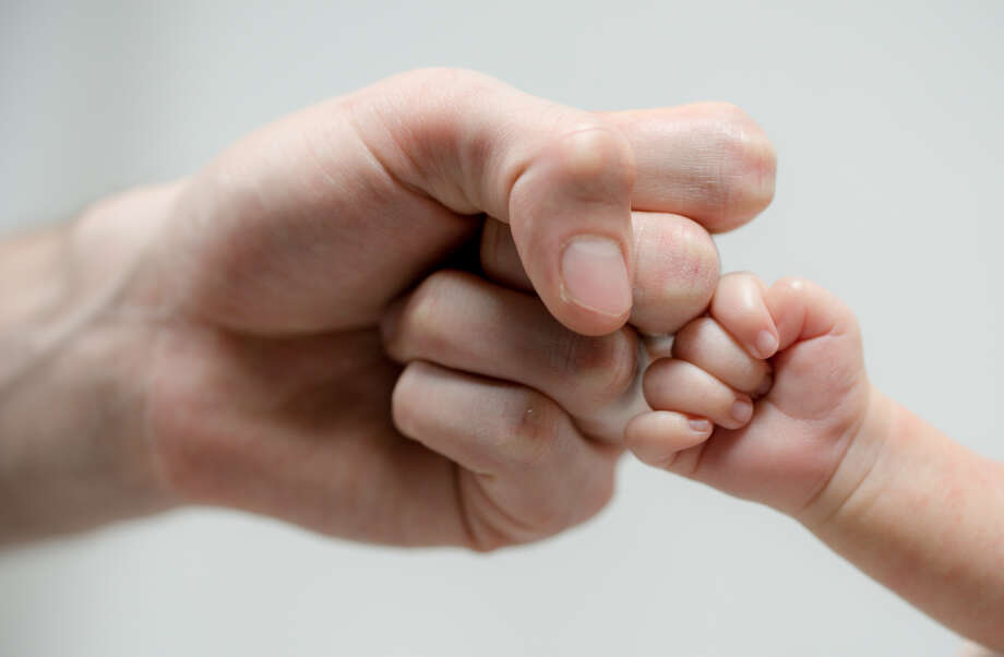 Fist of Dad and Newborn Baby. Photo: SimonDannhauer / Getty Images