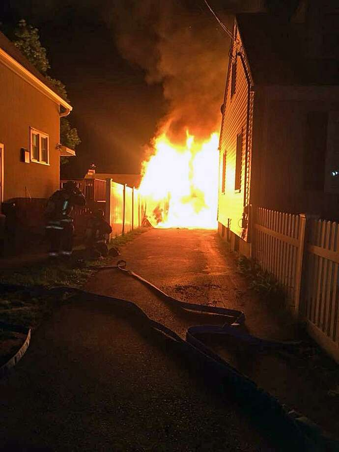 A car hit a detached garage in the 500 block of Birdseye Street in Stratford, Conn., in the early morning hours of June 16, 2018, and caught on fire. The garage was also engulfed in flames when firefighters arrived. Photo: Contributed Photo / Steve Michalovic / Contributed Photo / Connecticut Post Contributed