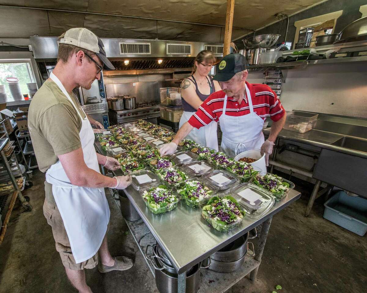 Chef Adam Begelow, left works on the production line at 9 Miles East Farm's food distribution business June 13, 2018 in Northumberland. (Skip Dickstein/Times Union)