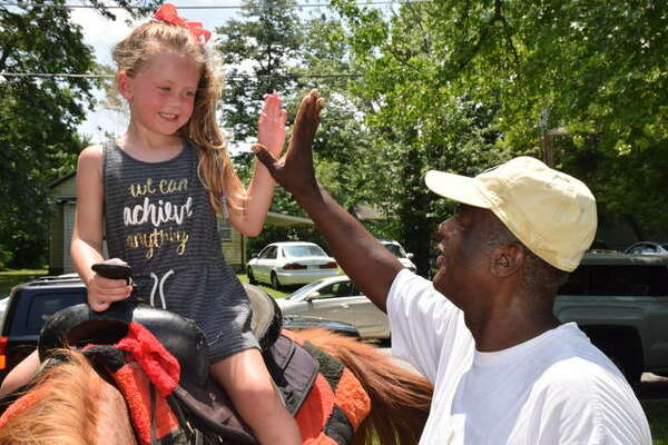 Four-year-old Bradley Nehls of Fenton, Missouri gives a high-five to Rickey Collins of St. Louis following a horseback ride at Killion Park.