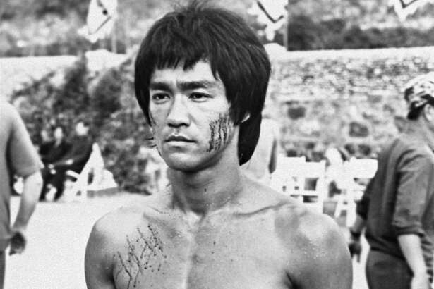 """** FILE ** Bruce Lee is shown in a scene from the 1973 film, """"Enter the Dragon,"""" completed shortly before the martial arts stars' death of brain edema in 1973. Bruce Lee fans are urging the Hong Kong government to help pay for a bronze statue to mark the actor's 65th birthday in November. (AP Photo/HO)"""