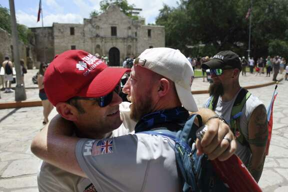 John Mayhead, left, embraces Kev Carr, a veteran of the British Royal Logistic Corps, at the The Alamo shrine after Carr and five other veterans completed a 15.7 mile walk from USAA to the shrine with the Walking With The Wounded/Walk of America expedition on Saturday, June 16, 2018. Six veterans from the US and the UK will continue their trek, which started in Los Angeles on June 2, to a conclusion in New York on September 6. The wounded veterans are hoping to raise awareness of mental health issues that British and American veterans face.