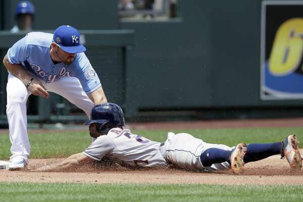 Houston Astros' Jose Altuve (27) is tagged out while trying to advance on a sacrifice fly by Kansas City Royals third baseman Mike Moustakas (8) during the first inning of a baseball game at Kauffman Stadium in Kansas City, Mo., Saturday, June 16, 2018. (AP Photo/Orlin Wagner)