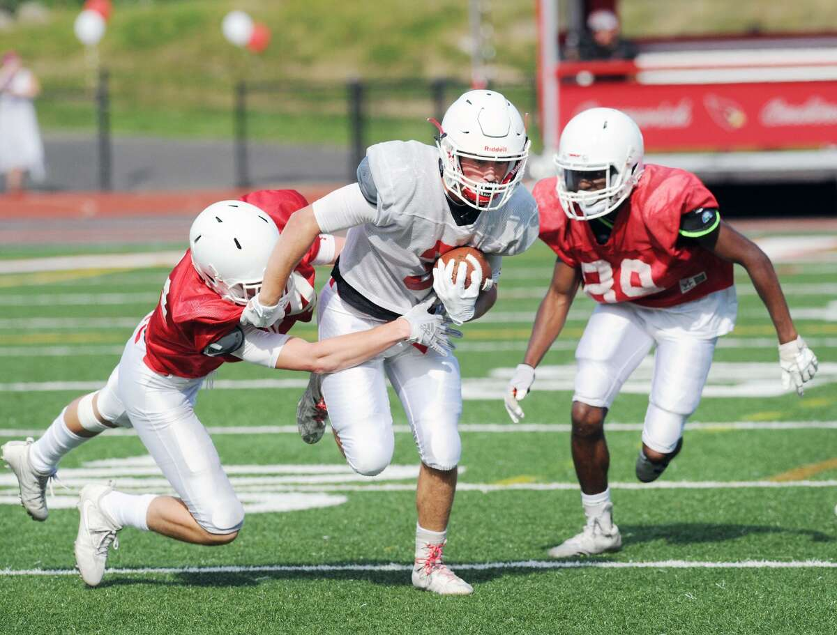 White receiver Lance Large of Greenwich, center, gets past two red-team defenders during the annual Red vs. White Greenwich High School football scrimmage at Cardinal Stadium in Greenwich, Conn., Saturday, June 16, 2018.