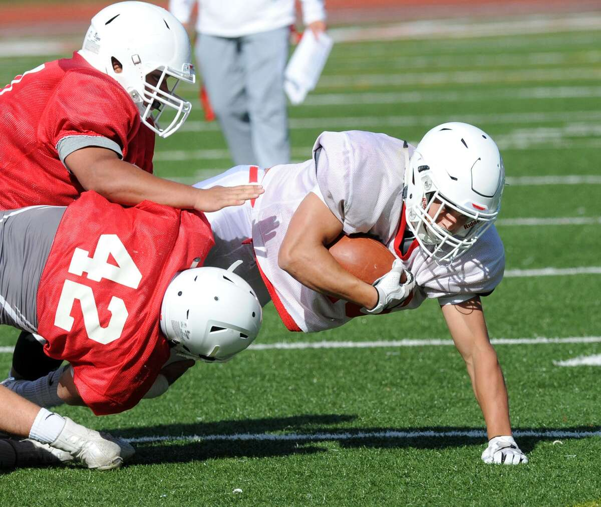 At right, Greenwich running back Tysen Comizio of the white team is tackled by Red team member Mozi Bici (#42) during the annual Red vs. White Greenwich High School football scrimmage at Cardinal Stadium in Greenwich, Conn., Saturday, June 16, 2018.