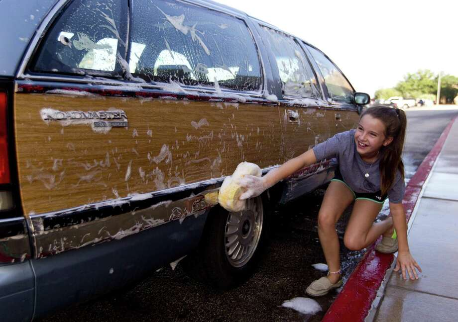 Gates Loryn laughs as she is accidently sprayed with water by Krista Dabney as Conroe FFA members host a car wash and garage sale to raise additional funds for the organization's trip to the Texas FFA State Convention on Saturday in Conroe. In addition to the $5,000 given by Conroe ISD, the organization will use the fundraiser to help with supplemental cost to the July convention in Fort Worth and future expenses. Photo: Jason Fochtman, Staff Photographer / Houston Chronicle / © 2018 Houston Chronicle