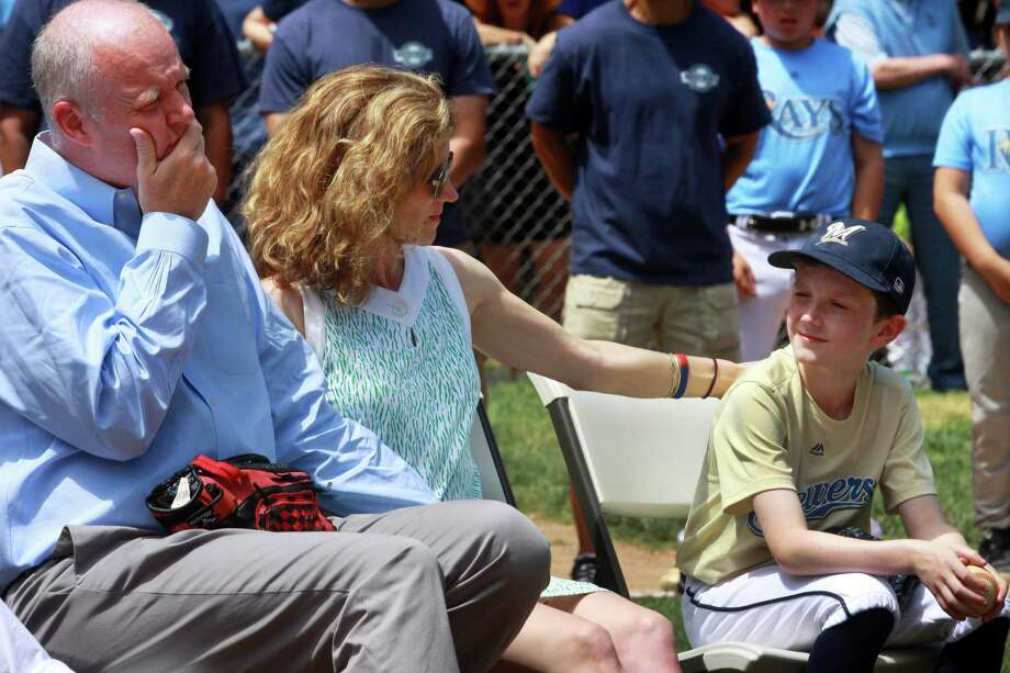 James and Angela Delorey, parents of Perrin Delory, 10, and Perrin's cousin Philip Sullivan sit as the Westport Little League Baseball community retires Perrin's jersey during a ceremony at Kowalski Field in Westport on Saturday. Delorey died after a car accident last week. Sullivan threw out the first pitch. Photo: Christian Abraham / Hearst Connecticut Media / Connecticut Post