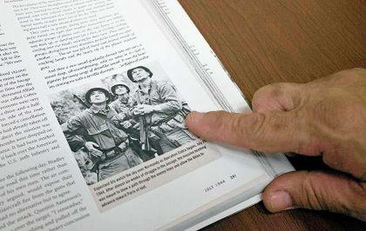 Bill Henson points out a photo of his father, William Henson, taking during Operation Cobra in World War II in the book companion to Ken Burns' documentary
