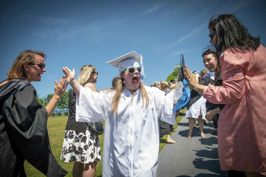 Alicia May Crossley is all smiles and high fives walking out of the Shepaug Valley High School Class of 2018 Commencement on Saturday, June 16, 2018. Photo: Trish Haldin / The News-Times Freelance