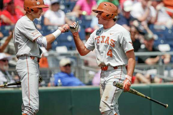 Texas' Tate Shaw (4) is greeted by David Hamilton, left, after he scored against Arkansas on a hit by Texas' Ryan Reynolds, who was out at first base, in the third inning of an NCAA College World Series baseball game in Omaha, Neb., Sunday, June 17, 2018. (AP Photo/Nati Harnik)