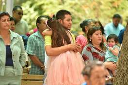Juan Torres hugs daughter Scarlett during a Father's Day Mass at Our Lady of Lourdes Grotto.