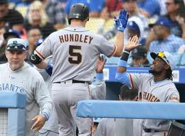 LOS ANGELES, CA - JUNE 17: Nick Hundley #5 of the San Francisco Giants is welcomed into the dugout after a 2 run home run against the Los Angeles Dodgers in the first inning at Dodger Stadium on June 17, 2018 in Los Angeles, California. (Photo by John McCoy/Getty Images)