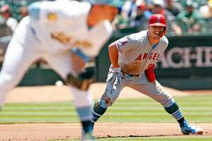 Los Angeles Angels' Mike Trout smiles while leading off first base against Oakland Athletics' starting pitcher Daniel Menhaden in 1st inning at Oakland Coliseum in Oakland, Calif. on Sunday, June17, 2018.