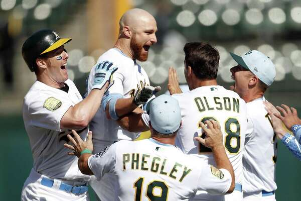 Oakland Athletics' Jonathan Lucroy is mobbed by teammates after getting the game -winning hit against Los Angeles Angels during A's 6-5 win in 11 innings at Oakland Coliseum in Oakland, Calif. on Sunday, June17, 2018.