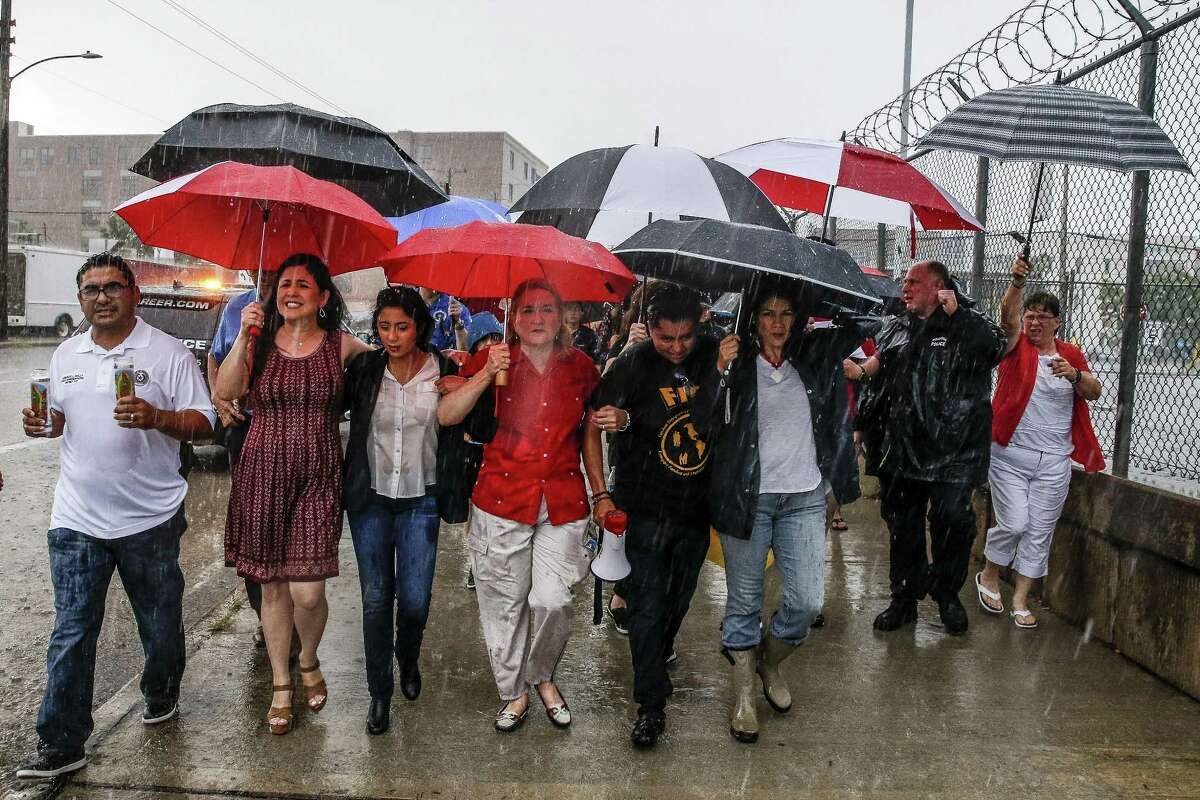 Texas senator Sylvia Garcia, center, links arms with protesters as they march through the rain during a Families Belong Together prayer vigil outside a facility near downtown Houston that has been leased to house unaccompanied immigrant children Sunday, June 17, 2018. (Michael Ciaglo / Houston Chronicle)