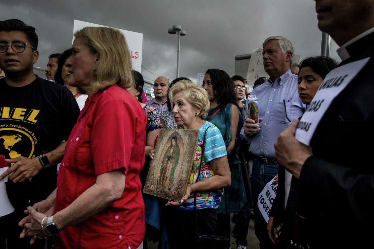 Protesters gather for a Families Belong Together prayer vigil outside a facility near downtown Houston that has been leased to house unaccompanied immigrant children Sunday, June 17, 2018.
