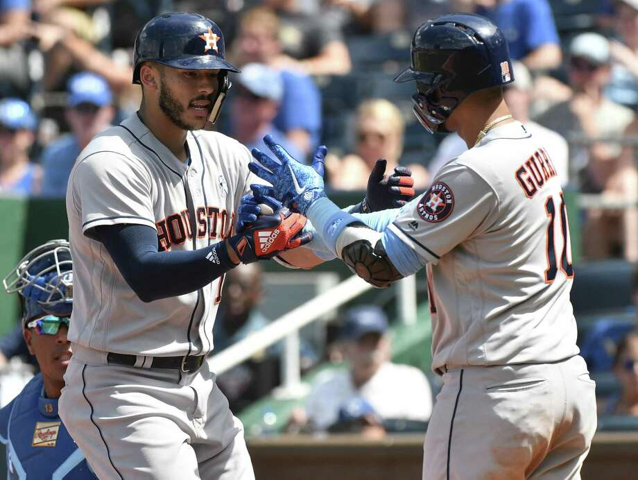 Carlos Correa, left, is greeted by Astros teammate Yuli Gurriel after starting the eighth inning with a game-tying home run off Royals reliever Brandon Maurer. Gurriel would follow with a single and score the go-ahead run on a single by Evan Gattis. Photo: Ed Zurga, Stringer / Getty Images / 2018 Getty Images