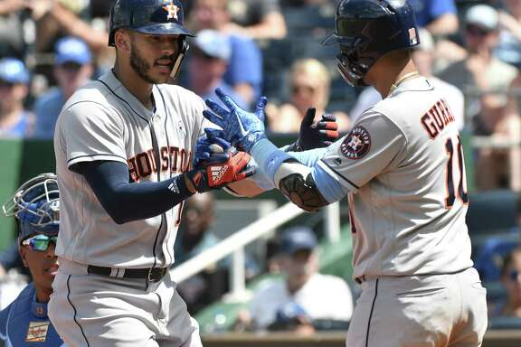Carlos Correa, left, is greeted by Astros teammate Yuli Gurriel after starting the eighth inning with a game-tying home run off Royals reliever Brandon Maurer. Gurriel would follow with a single and score the go-ahead run on a single by Evan Gattis.