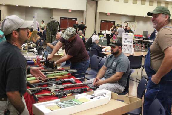 Dennis Neitsch (right) discusses his guns for sale with a visitor at the Outdoor Expo on June 16.