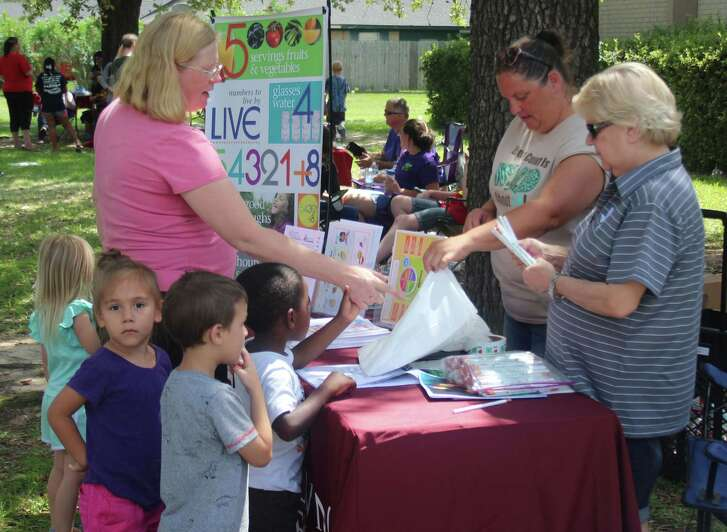 JoLynn Reynolds (right) and Kristy Fruia (second from right) pass out information on the Texas A& Agrilife Extension 4-H office during the Community Kick-Off at Austin Memorial Library on June 13.