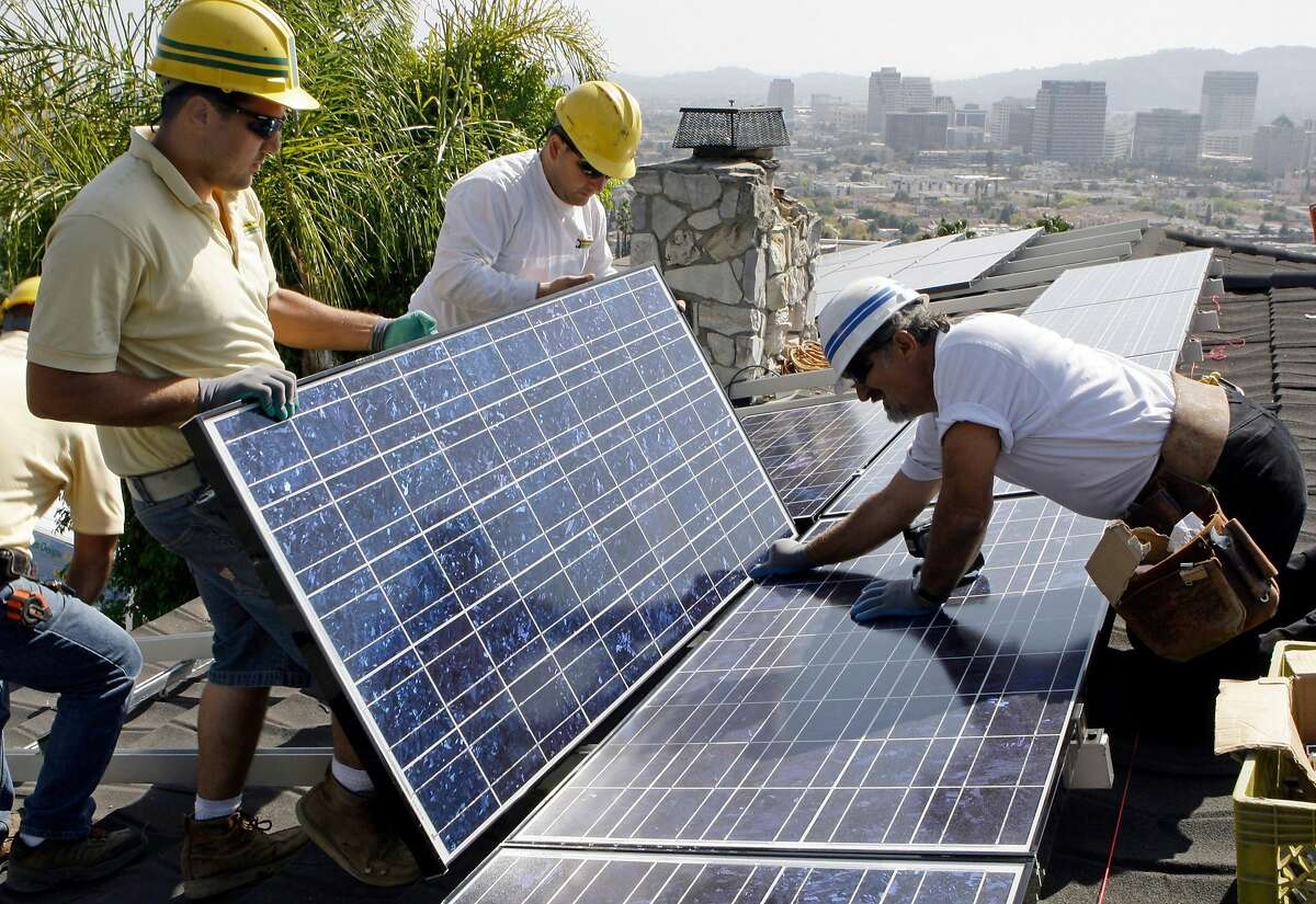FILE - In this file photo taken March 23, 2010, installers Arin Gharibian, left, Hayk Mkrtchayan, and team leader Edward Boghosian, right, all employees of California Green Design, assemble solar electrical panels on the roof of a home in Glendale, Calif. Homeowners on the hunt for sparkling solar panels are lured by ads filled with images of pristine landscapes and bright sunshine, and words about the technology�??s benefits for the environment - and the wallet. What customers may not know is that there�??s a dirtier side. While solar is a far less polluting energy source than coal, many panel makers are nevertheless grappling with a hazardous waste problem. Fueled partly by billions in government incentives, the industry is creating millions of solar panels each year and, in the process, millions of pounds of polluted sludge and contaminated water. (AP Photo/Reed Saxon, file)