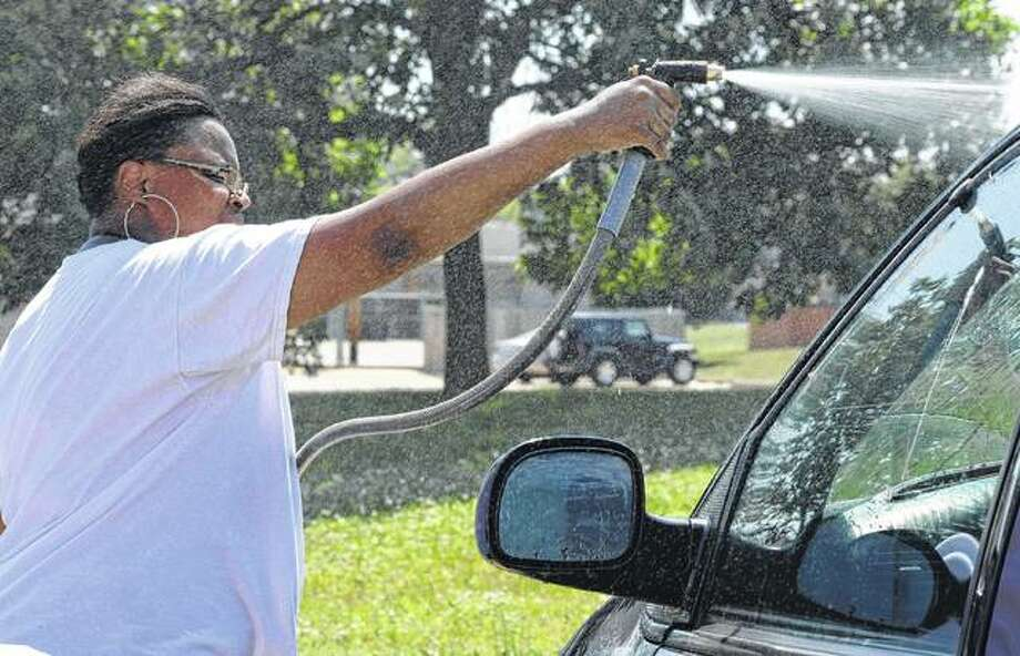 Nicole Flowers of Jacksonville washes a van during a car wash at Autozone to raise funds for Community Temple Church. Photo:       Samantha McDaniel-Ogletree | Journal-Courier