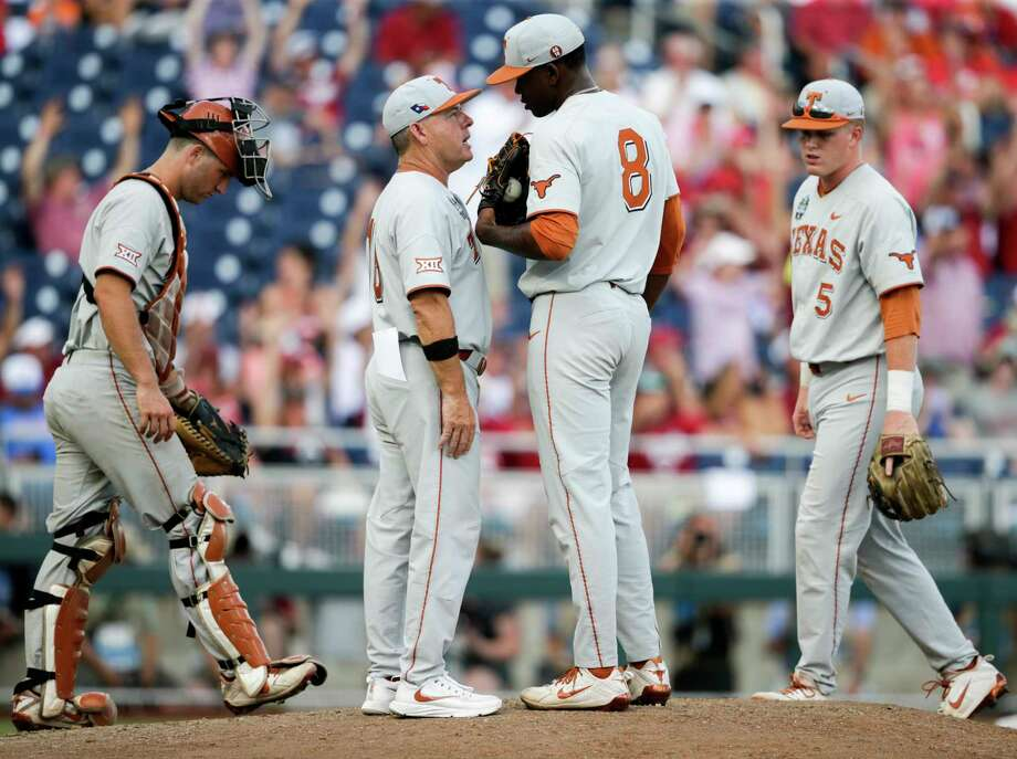 Texas coach David Pierce, second left, talks to pitcher Kamron Fields (8) on the mound, with catcher DJ Petrinsky, left, and Ryan Reynolds (5) joining in, in the sixth inning of an NCAA College World Series baseball game against Arkansas in Omaha, Neb., Sunday, June 17, 2018. Arkansas won 11-5. (AP Photo/Nati Harnik) Photo: Nati Harnik, Associated Press / Copyright 2018 The Associated Press. All rights reserved.