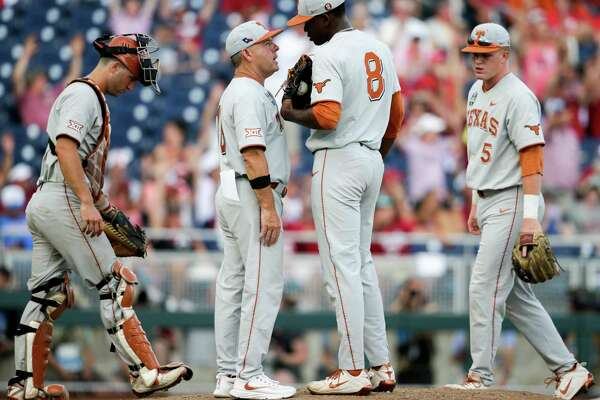Texas coach David Pierce, second left, talks to pitcher Kamron Fields (8) on the mound, with catcher DJ Petrinsky, left, and Ryan Reynolds (5) joining in, in the sixth inning of an NCAA College World Series baseball game against Arkansas in Omaha, Neb., Sunday, June 17, 2018. Arkansas won 11-5. (AP Photo/Nati Harnik)