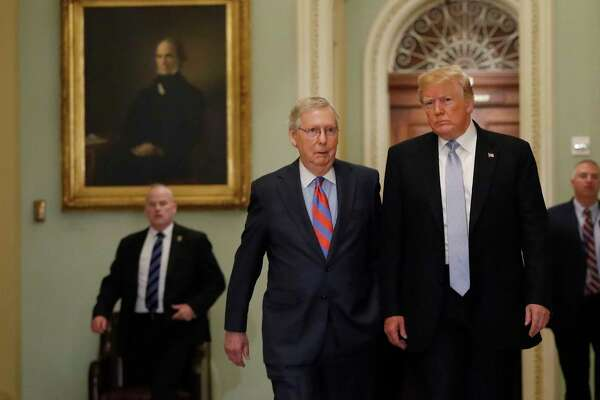 President Donald Trump (right) walks with Senate Majority Leader Mitch McConnell, R-Ky., before attending the weekly Senate luncheons on Capitol Hill in Washington on May 15, 2018.