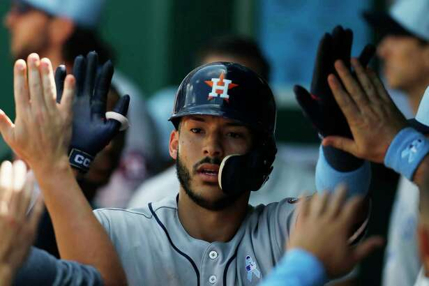 Houston Astros' Carlos Correa celebrates in the dugout after hitting a home run to tie the Kansas City Royals in the eighth inning of a baseball game at Kauffman Stadium in Kansas City, Mo., Sunday, June 17, 2018. (AP Photo/Colin E. Braley)