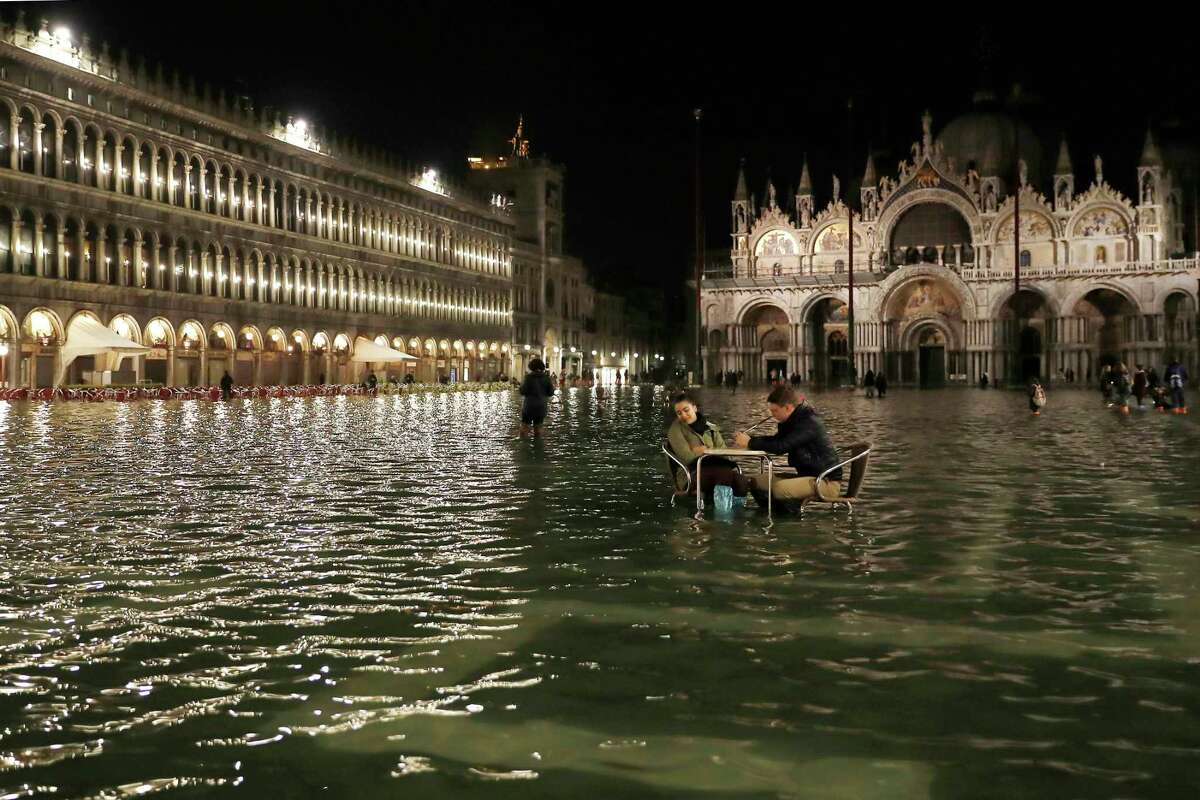 In this Friday, March 30, 2018 file photo, people sit in a flooded St. Mark's Square in Venice, Italy, as high tides inundated the city. Across the globe seas have risen about three inches in 2018 since 1993.