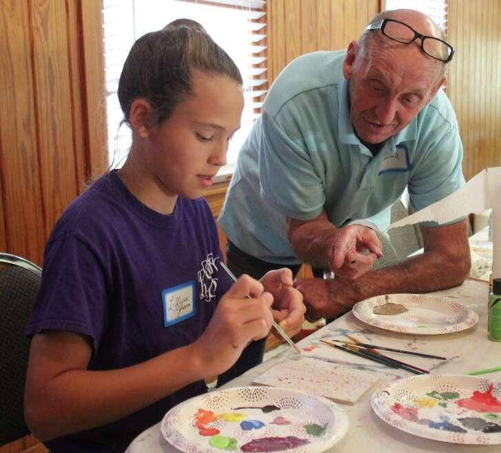 Jonnie Lee (right) teaches Lillian Johnson (left) on how to paint a small, wooden canvas at the Kids Art Camp on June 16.