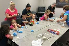 Children at the Coldspring Area Public Library's June 13 Summer Reading program engage in creating musical instruments out of household items.