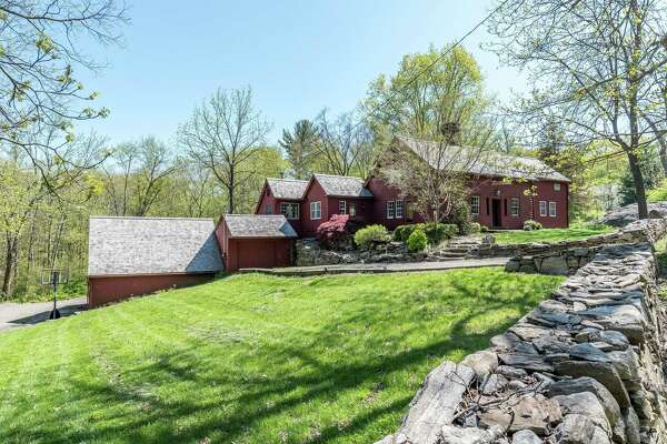 The red antique colonial house at 43 Old Easton Turnpike was built in 1710 but contains modern amenities and vintage charm.