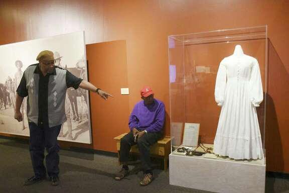 """Actor Carl Brooks points to a dress sewn and worn by freed slave Sarah Tate in the 1860s. Playwright Eugene Lee, who wrote """"Ode to Juneteenth,"""" sits by the dress, which is on display at the Witte Museum."""