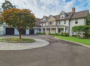 The gray colonial house at 6 Cob Drive contains 15 room and 7,700 square feet of living space with elegant formal spaces and comfortable places to relax inside an out.