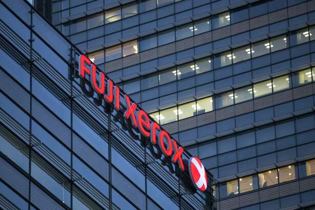 The logo of Fuji Xerox Co., the joint venture between Fujifilm Holdings Corp. and Xerox Corp., is displayed outside the company's headquarters in Tokyo, Japan. Photographer: Tomohiro Ohsumi/Bloomberg
