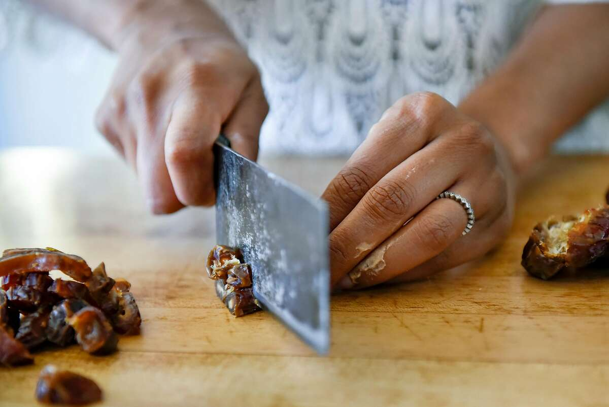 Just Date Syrup creator Sylvie Charles chops up fresh dates as she makes tahini-date chocolate chip cookies at her home in San Francisco, Calif., on Tuesday June 12, 2018.