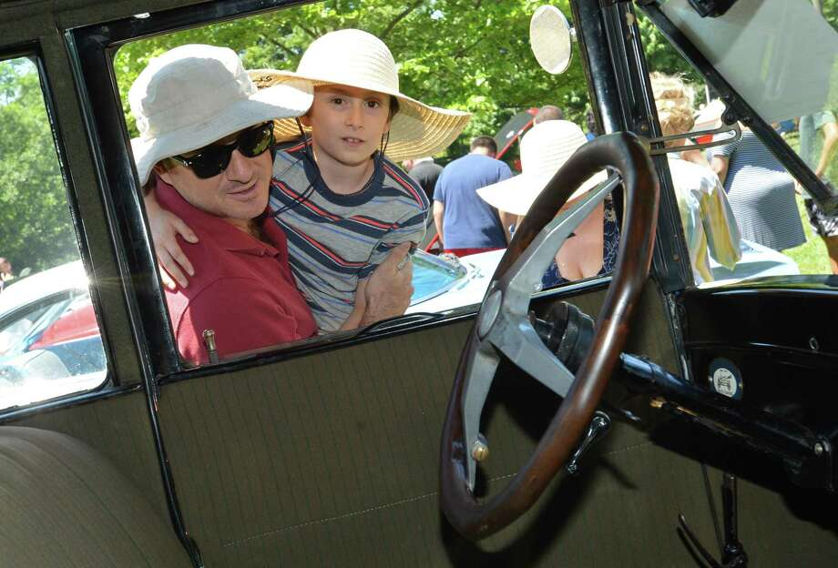8 yr-old Harrison West gets a lift up from dad Josh to look inside an antique car at the 4th annual New England Auto Museum Father's Day Car Show on Sunday at Mathews Park in Norwalk. A major fundraiser for the New England Auto Museum, the event attracted more than 100 cars that spread out on the lawn with the Lockwood-Mathews Mansion as a backdrop. Photo: Alex Von Kleydorff / Hearst Connecticut Media / Norwalk Hour