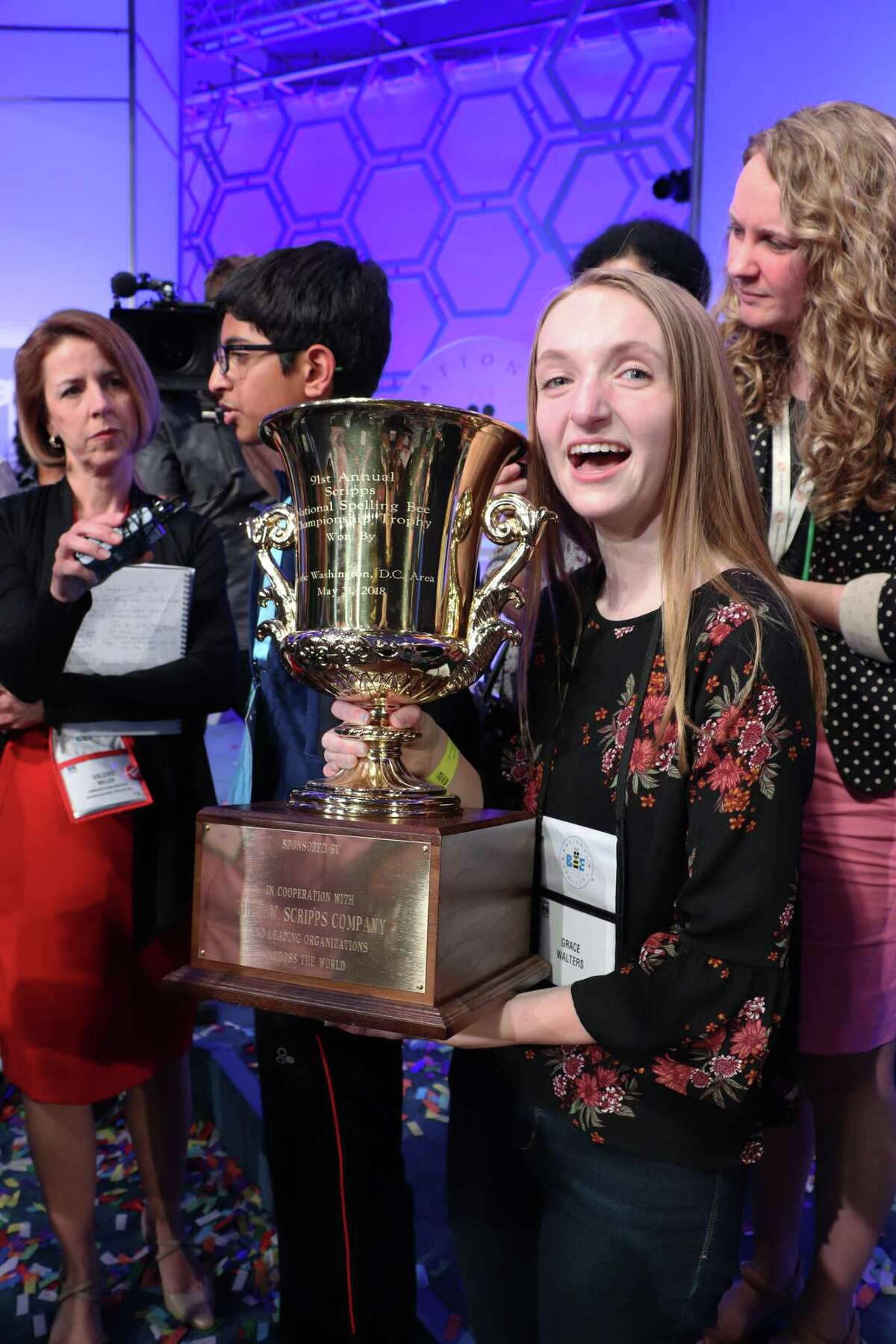 Grace Walters, 16, a Covenant Christian School student, holds the 2018 Scripps National Spelling Bee trophy while her spelling student, Karthik Nemmani, does interviews after winning the 2018 Scripps National Spelling Bee on May 31. Walters has coached Nemmani since September in preparation for the contest.